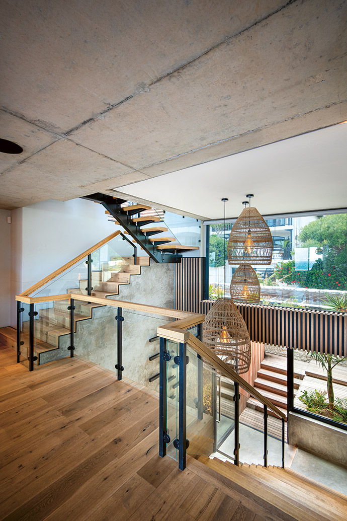 The use of timber on the floors, walls and staircases creates a parallel with the path that takes the owners down a tree-lined walkway to the beach. Large hanging pendants by Weylandts add to the feel as they float above the entrance foyer. The floor finish is by Oggie Hardwood Flooring.