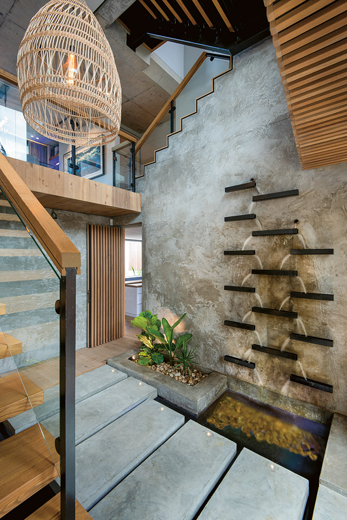 The foyer welcomes visitors with a koi pond and a wall water feature, before leading them up the stairs to the main living area of the upper home. The hidden door in the corner is the only internal link between the two residences.
