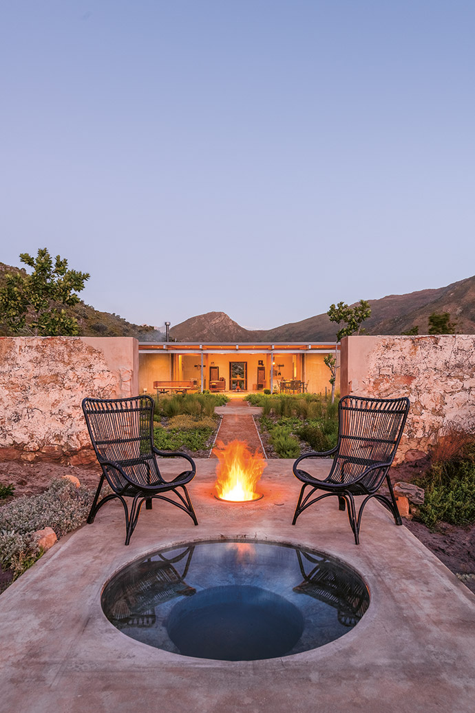 Charcoal rattan wing-backs add a note of drama near the firepit.
