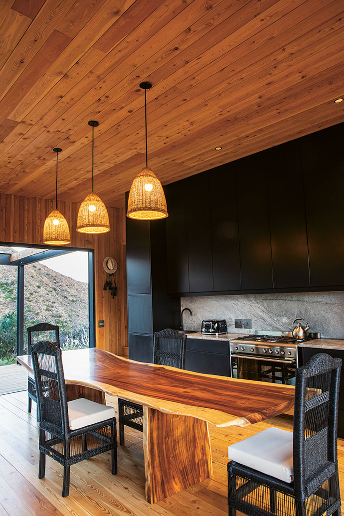 The kitchen features a wooden table custom-made from materials supplied by Rare Woods, and chairs from Malawi Cane.