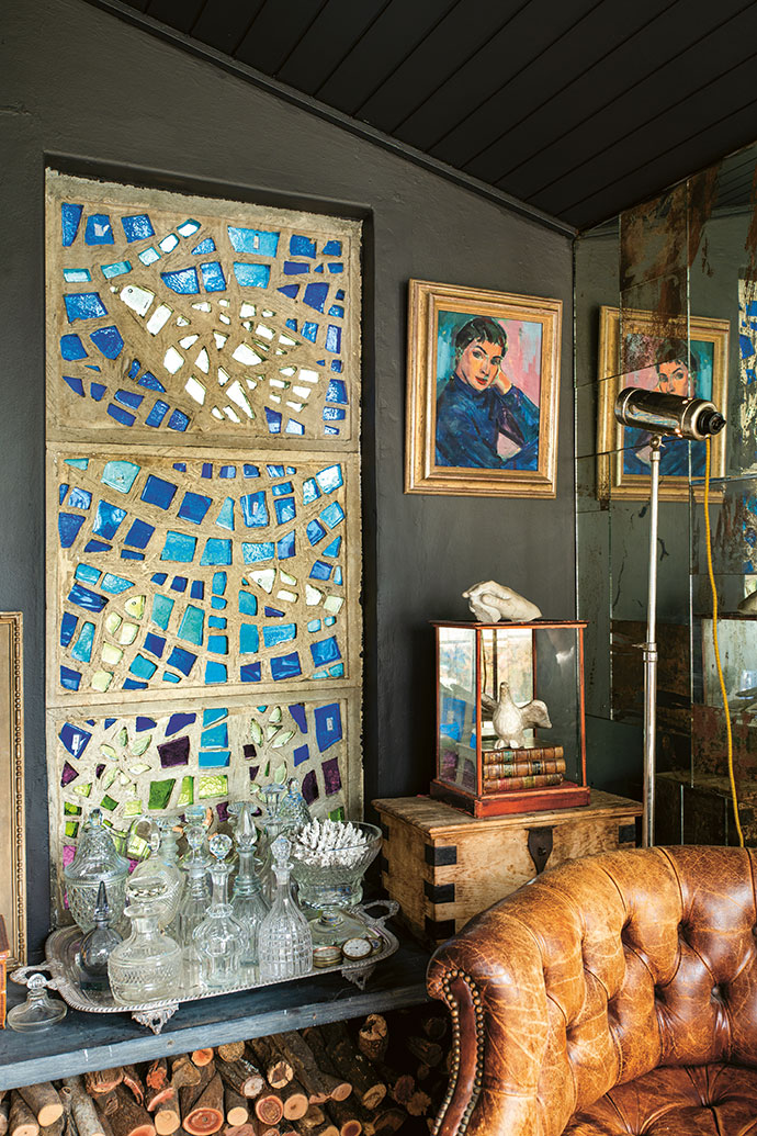 """Leo Theron's stained-glass window picks up on the same artist's portrait, titled Wendy. """"I like heavy, solid Georgian and Victorian glass,"""" says David of his collection of decanters."""