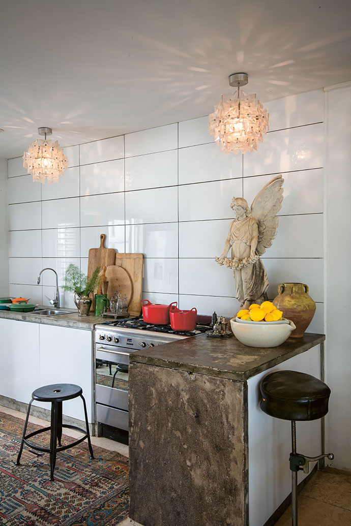 The faceted, acrylic 1980s chandeliers match the one in the dining area, which is adjacent to the kitchen counter.