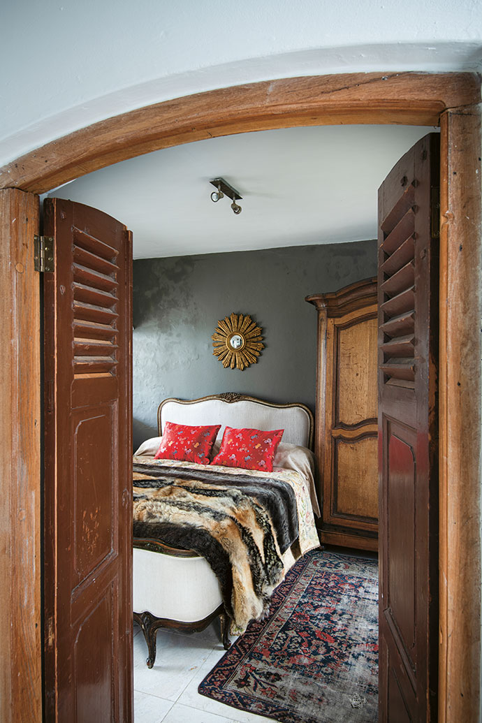 Reclaimed shutters have been repurposed as doors to the guest bedroom, where an antique French wardrobe and Persian rug add warmth and charm.