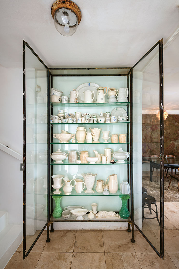 A custom-built industrial-style cabinet stands in the entrance hall, and holds various white ceramic pieces collected over the years.