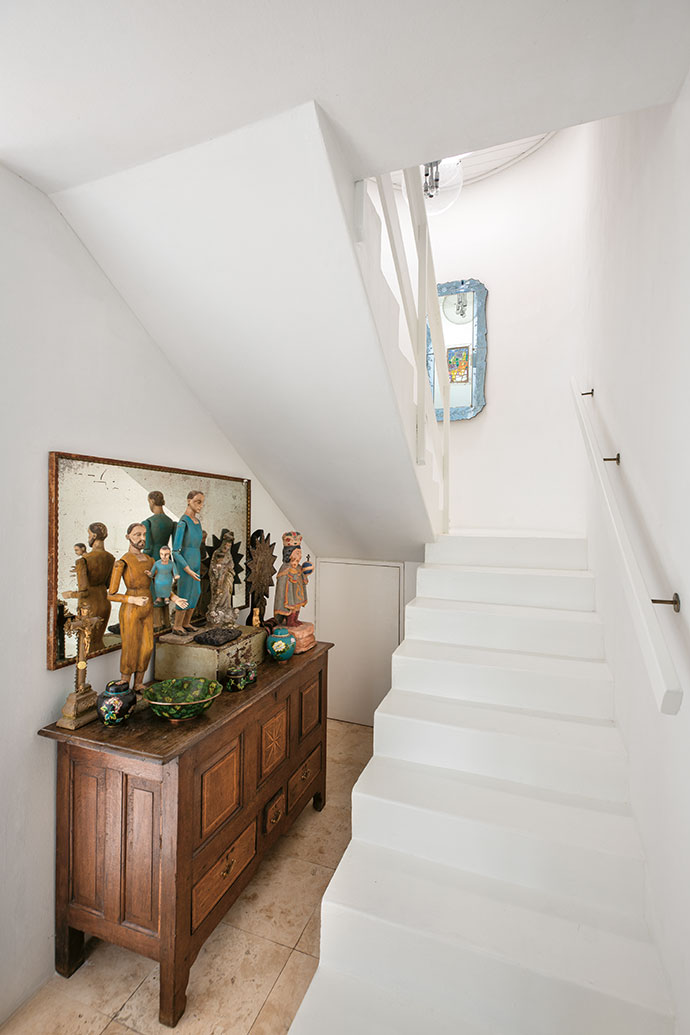 Underneath the staircase is an antique Dutch server that displays ecclesiastic figurines sourced during David's travels to Argentina, Peru and the Philippines.