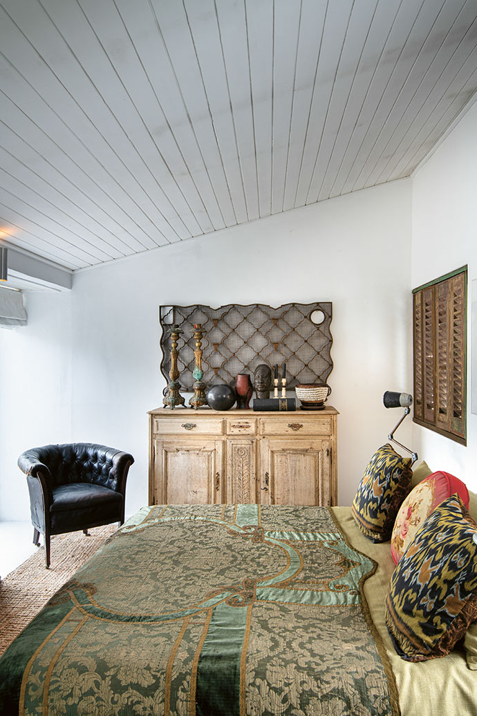 In the master bedroom, a tablecloth has been transformed into a bedspread, and an iron heater grid has become a wall feature. The Georgian leather chair is as much of a statement as the candelabras from Buenos Aires, the Zulu pot, the shell basket and the bronze Nigerian bust.