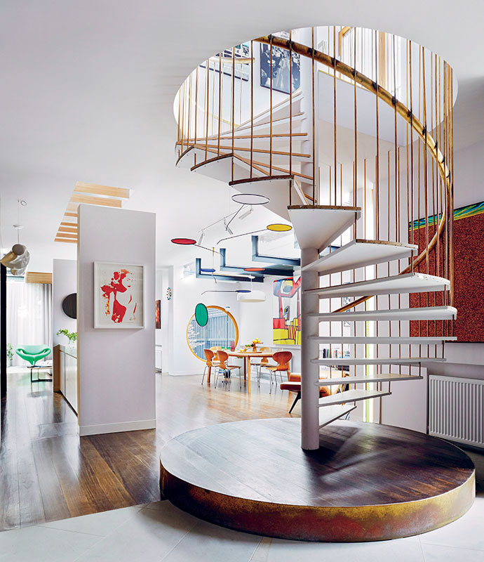 The extension's living area features a spiral staircase on a plinth, with a brass handrail and rod cage. From here, the flooring transitions from limestone to solid Tasmanian oak. The Joel Hotchkiss Lumen mobile was acquired at New York's Guggenheim Museum.