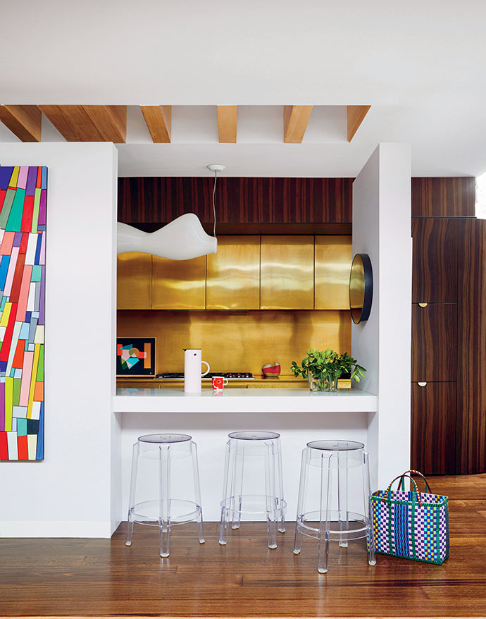 Brass casts a warm glow over the rear cabinetry in the kitchen, while timber battens reinforce the importance of wood in the home. The Ghost stools are by Philippe Starck for Kartell, and the artwork on the rear bench is by Anna Cole.