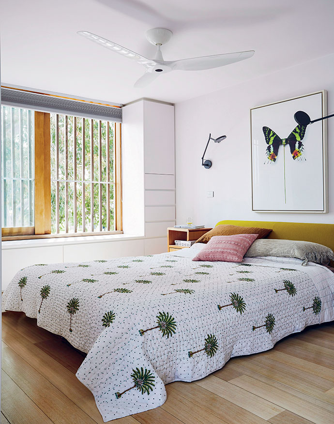 An artwork by street artist D*Face adds to the bedroom's nature-based aesthetic.