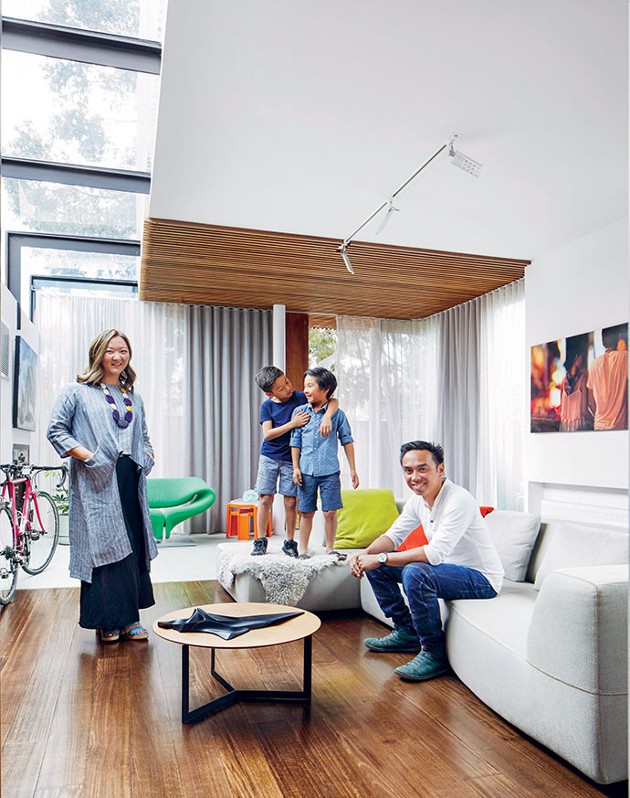 Owners Susan and Michael encourage sons Jasper, 9 (left), and Mannix, 7, to use all the furniture in this art-filled space. In fine weather, they open the curtains and let the full-height glazing bring the green of the garden inside.