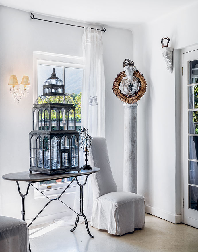 A unique entrance hall sets the tone for owner Marti Heyns-Foster's interiors. When walls are crisply white, carefully selected eccentricities such as a Gothic birdcage and a wreathed bust on a tall marble plinth don't seem like clutter.