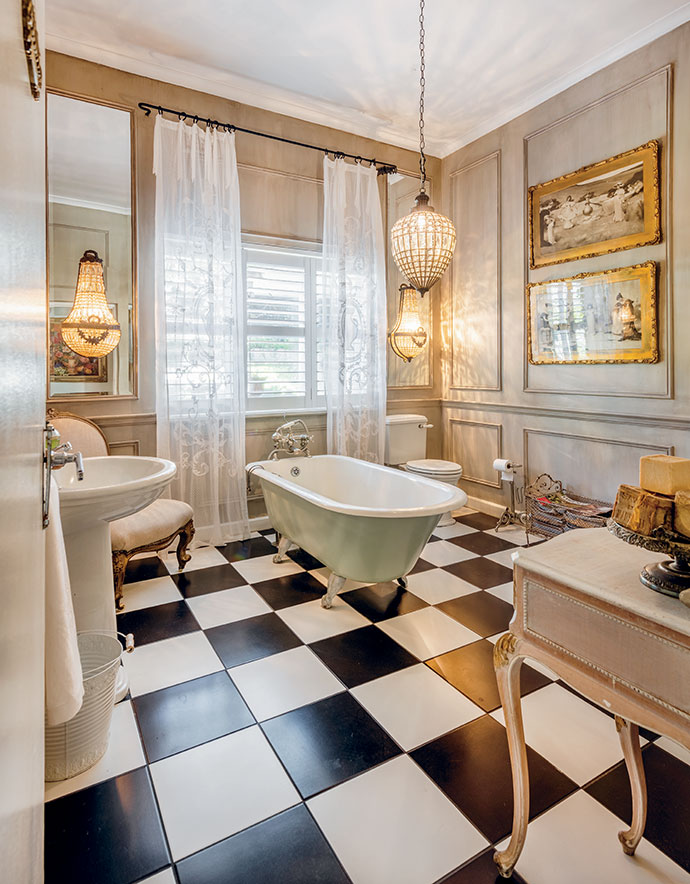 Wall panelling and classic blackand-white flooring ground the glamorous bathroom, while diaphanous drapes and a pendant chandelier add femininity.
