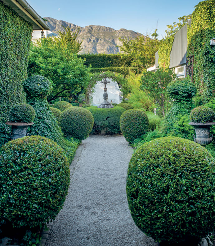 The front formal French garden – complete with topiaries – creates a manicured entrance, and complements the Gothic-style pool in the back garden.