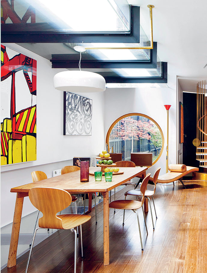Susan draws inspiration from her home's vibrant artworks, including these by (from left) Jasper Knight, Mayonaize and Melinda Harper, as well as from the beautiful Japanese maple outside the pivoting window. The Messmate dining table is by sustainable furniture designer Brad Nicholls.