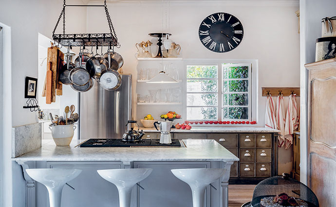 The hanging pot rack and apothecary storage unit in the open-plan space are oh-so-French.