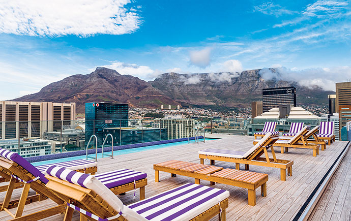 """One of the two pool areas – with a pool by Pool Designs, decking by Decks4Life and loungers by Metriplex Retail – that cantilever off the back """"steps"""" of the building to offer unobstructed city views."""