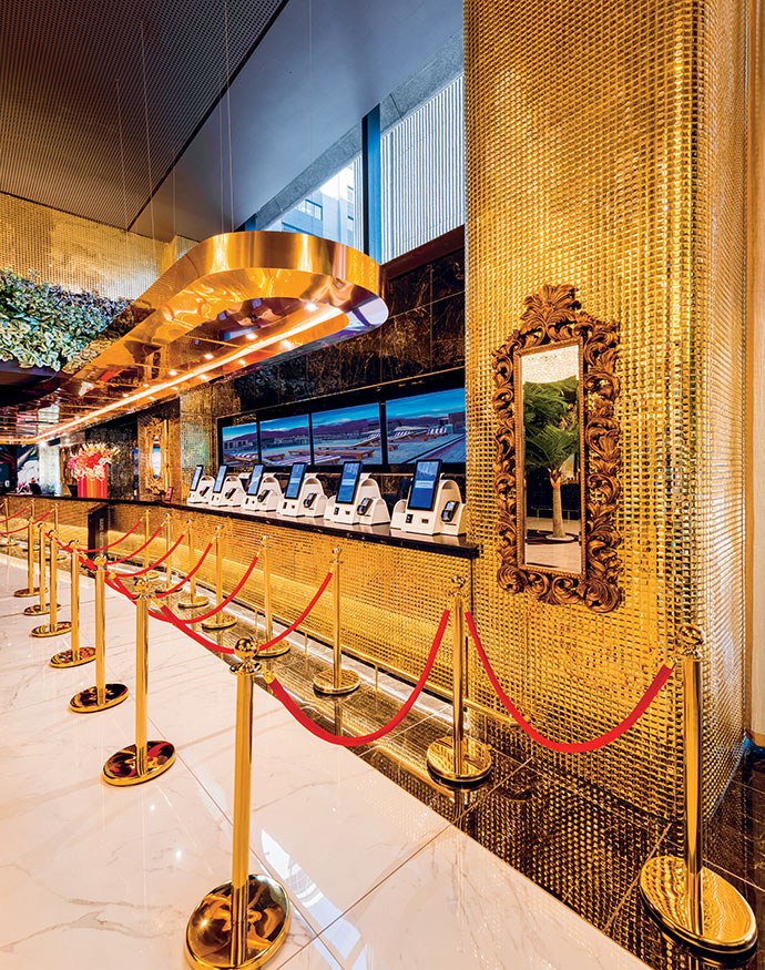 The self-check-in area by Bright Horse goes for gold with a custom LED light fitting by Noero Architects, mosaic tiles by Limegreen and waiting rope stands by The Silver Flair.