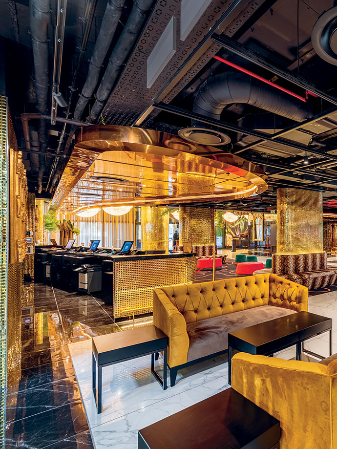 In sharp relief to the lobby's ornate decor, he exposed services in its ceiling were transformed into an industrial-chic showpiece with clever red-and-black colour blocking.