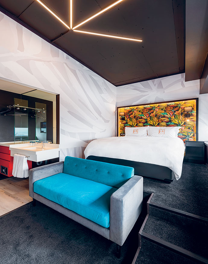 Standard rooms are entered via galley bathrooms. The sleeping/ lounge area is decorated with Sasi wallpaper, quirky lights by Eagle Lighting, a Hertex-upholstered headboard designed by Noero Architects, and a sleeper couch by PH Design.