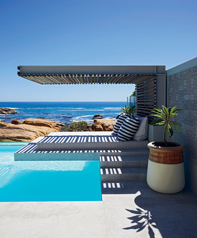 An outdoor daybed is flanked by ceramic-andtimber Soma planters from Indigenus.