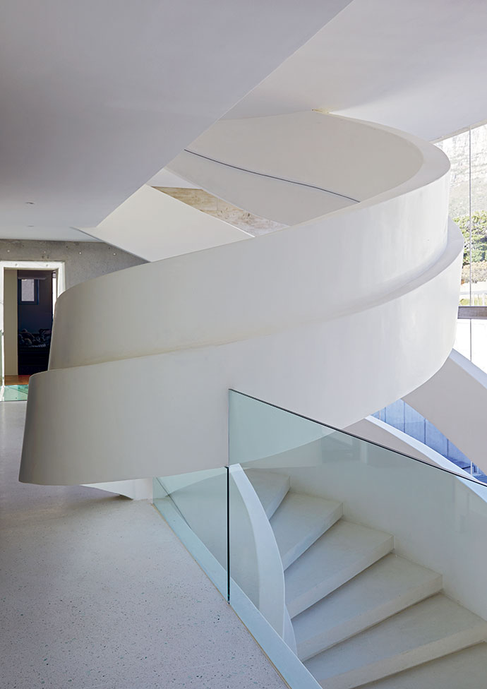 The staircase as seen from the first floor, where glass balustrades provide safety without cluttering the space.