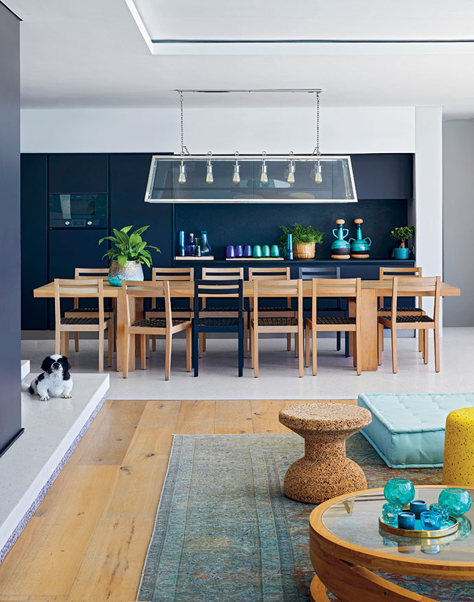 The kitchen joinery is black, creating the perfect backdrop for the warmth of a wooden dining table and chairs by James Mudge, a light fixture from Morgan Day Lighting, and a collection of colourful glassware – all 100% recycled in a collaboration between Wiid Design and Ngwenya Glass in Swaziland.
